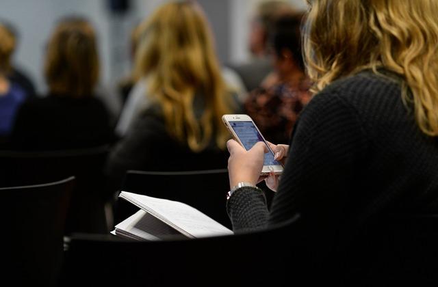 Dziewczyna przegląda informacje w smartfonie podczas wykładu