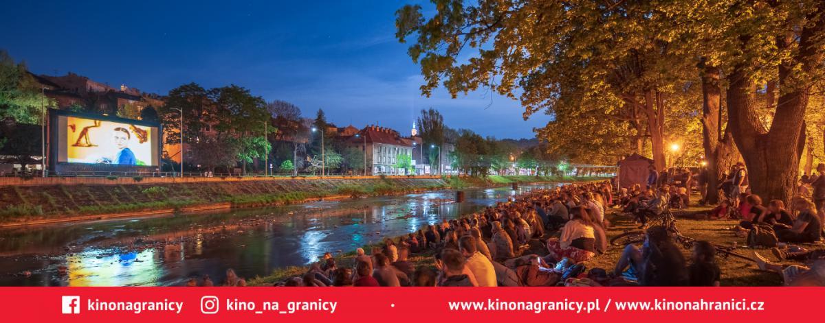 Uczestnicy przeglądu filmowego oglądają projekcję filmu, wydarzenie odbywa się w plenarze, ekan umieszczony jest po jednej stronie rzeki, uczestnicy siedzą na drugim brzegu
