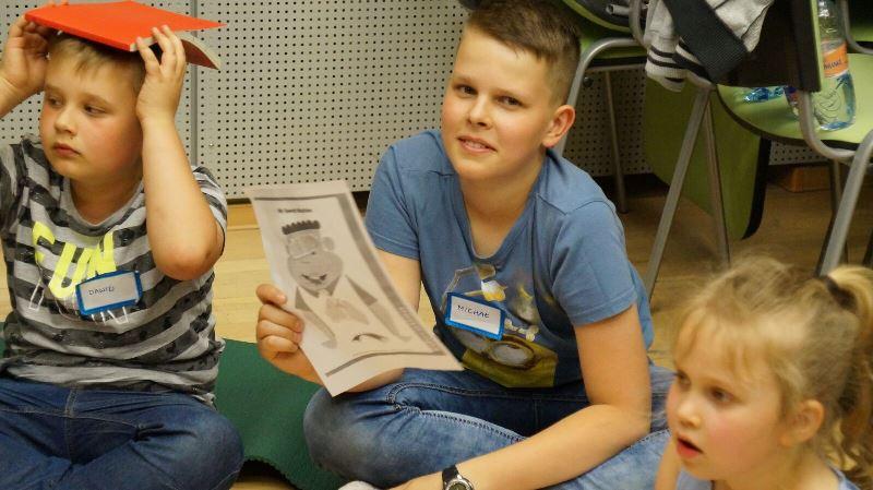 trójka dzieci: jeden z chłopców trzyma książkę na łowie, drui w ręce trzyma kartkę papieru, a dziewczynka patrzy przed siebie