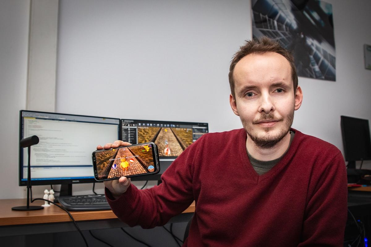 Mężczyzna prezentuje grafikę gry na smartfonie