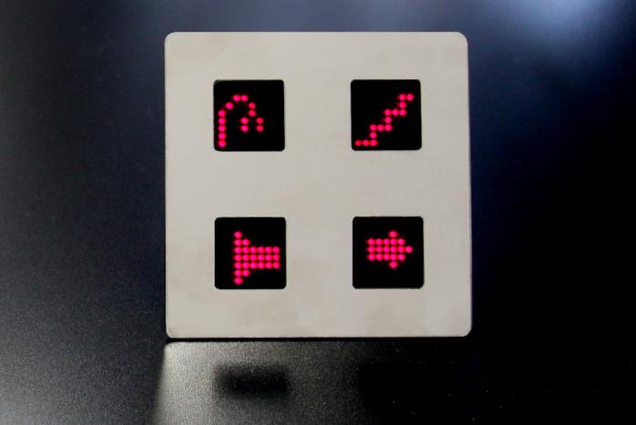 Włącznik dotykowy na czarnym tle. Składa się z czterech podświetlonych paneli symbolizujących kolejno: lampę, schody, wzmacniacz i strzałkę