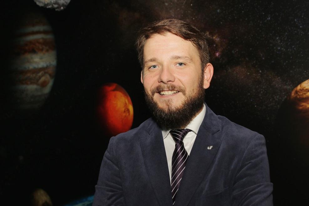 Zdjęcie portretowe mężczyzny, w tle fragment układu planetarnego