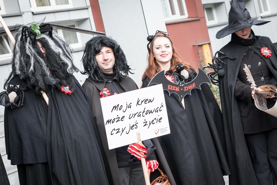 """Przebrani za wampiry uczestniczy wydarzenia, jedna z osób trzyma w ręce tablicę z napisem """"Moja krew może uratować czyjeś życie"""""""