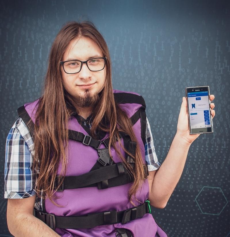 Mężczyzna w fioletowej kamizelce prezentuje aplikację na smartfonie