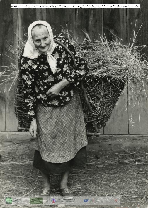 Kobieta niesie na placach kosz z sianem