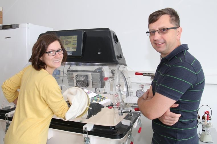 Dr inż. Justyna Knapik-Kowalczuk oraz prof. zw. dr hab. Marian Paluch prezentują działanie Glowboxa – specjalistycznej komory rękawicowej służącej do utrzymywania stałych warunków wilgotności oraz temperatury