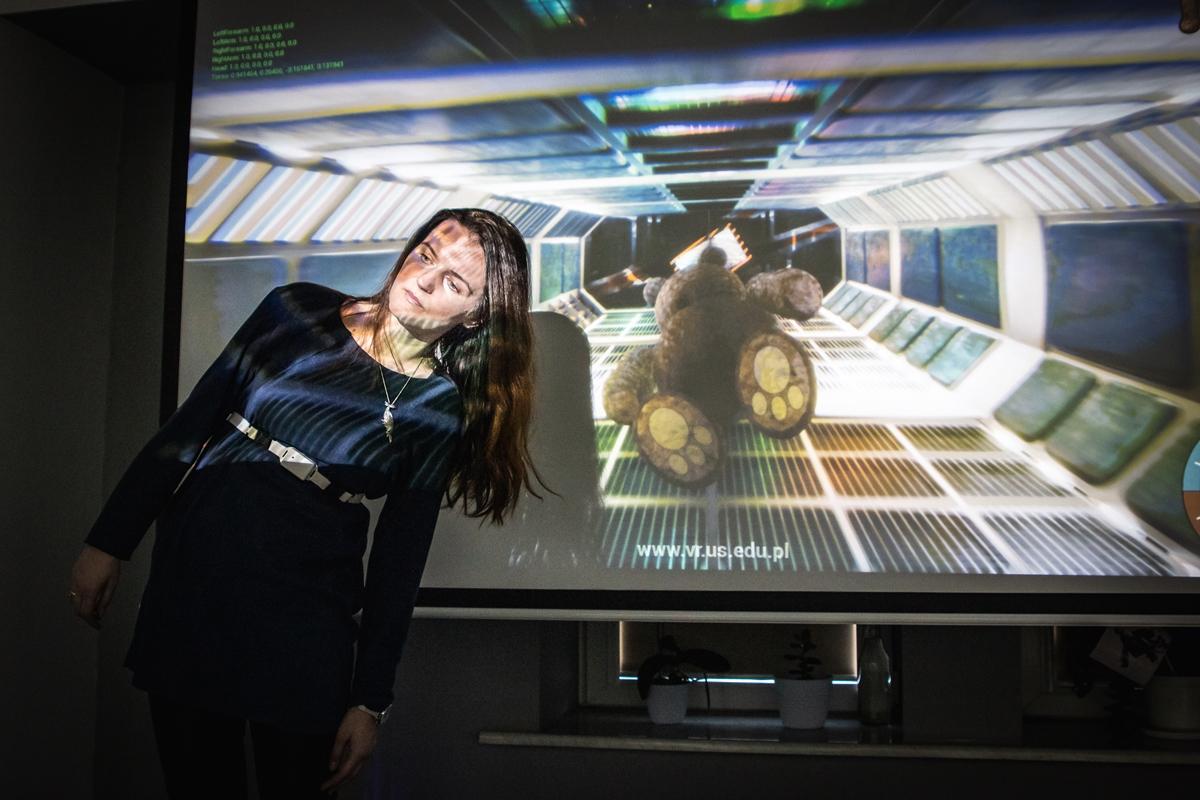 Kobieta wyginająca tułów, w tle ekran, na którym widać lecącą postać misia