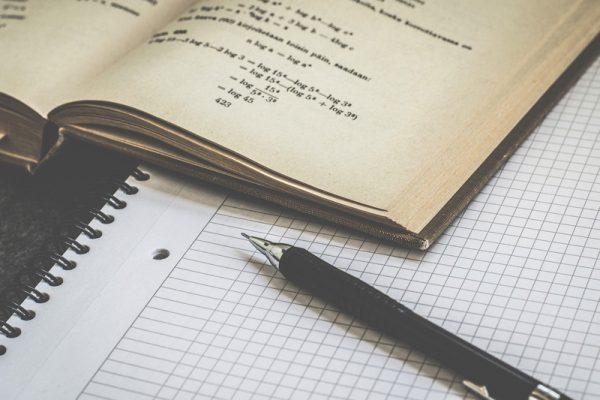 długopis, zeszyt, książka z zadaniami matematycznymi