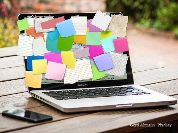 laptop na stole, na jego ekranie przyklejone są kolorowe karteczki, obok laptopa leży telefon/laptop on a table, colourful stickers on the screen, mobile phone next to the laptop