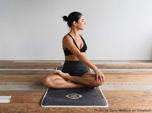 kobieta siedzi na macie, ćwiczy jogę
