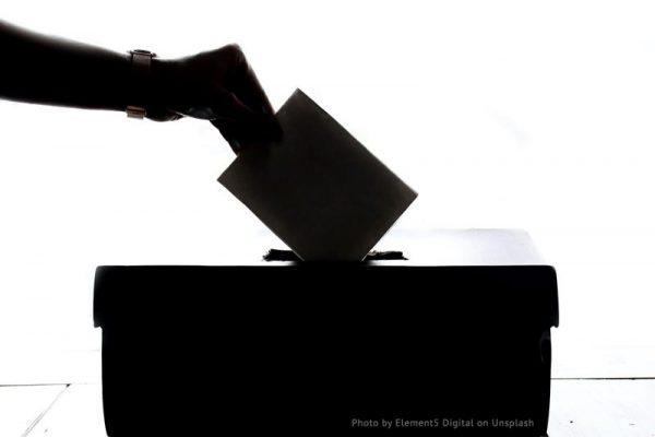 osoba wrzuca kartkę do urny wyborczej