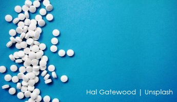 Białe tabletki na niebieskim tle