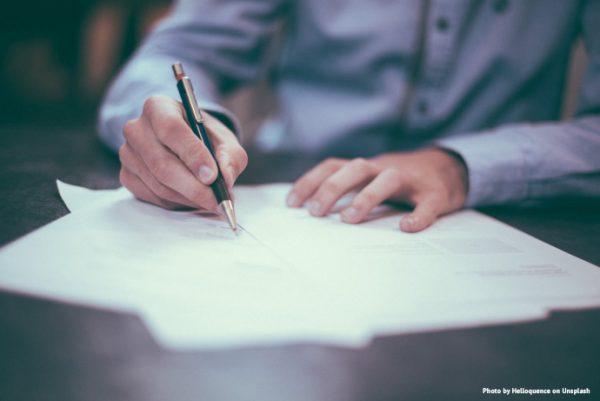 Osoba podpisująca dokument, zbliżenie na dłonie