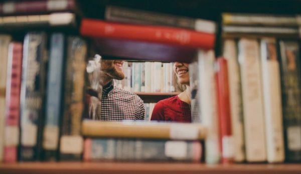 Książki na regale, w głębi dwoje uśmiechniętych ludzi