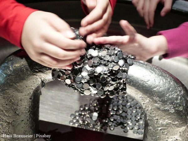 Dzieci przeprowadzają eksperyment z magnesami, na zdjęciu widać ręce dzieci i magnesy