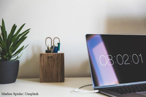 na biurku leżą: laptop z wyświetloną godziną, roślina w doniczce, przybornik z długopisami i nożyczkami