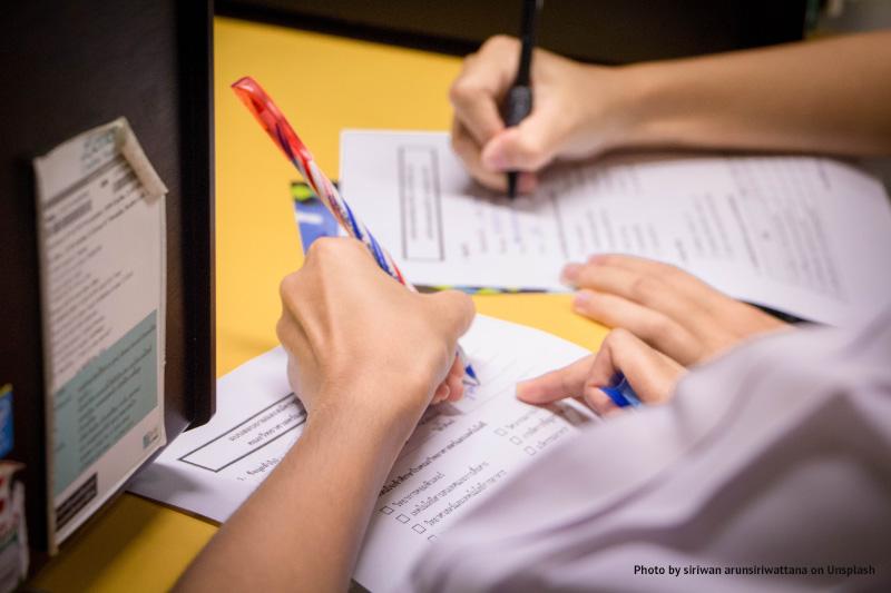 Osoby wykonujące notatki (zbliżenie na dłonie)