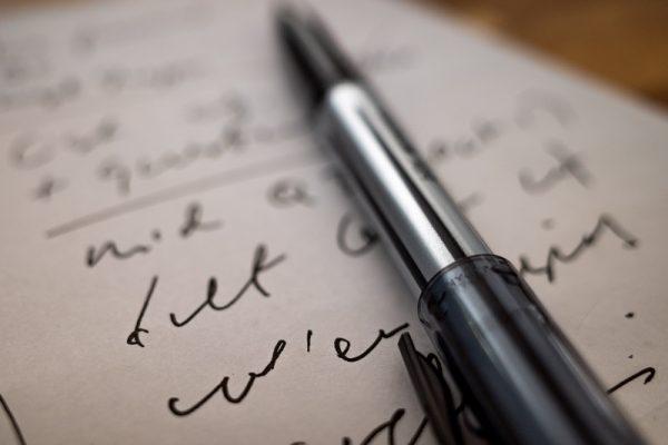 Długopis leżący na zapisanej kartce papieru