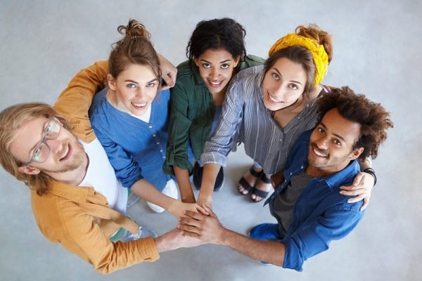 Kilkoro przyjaznych ludzi różnych narodowości patrzy w górę do obiektywu, trzymając się za ręce