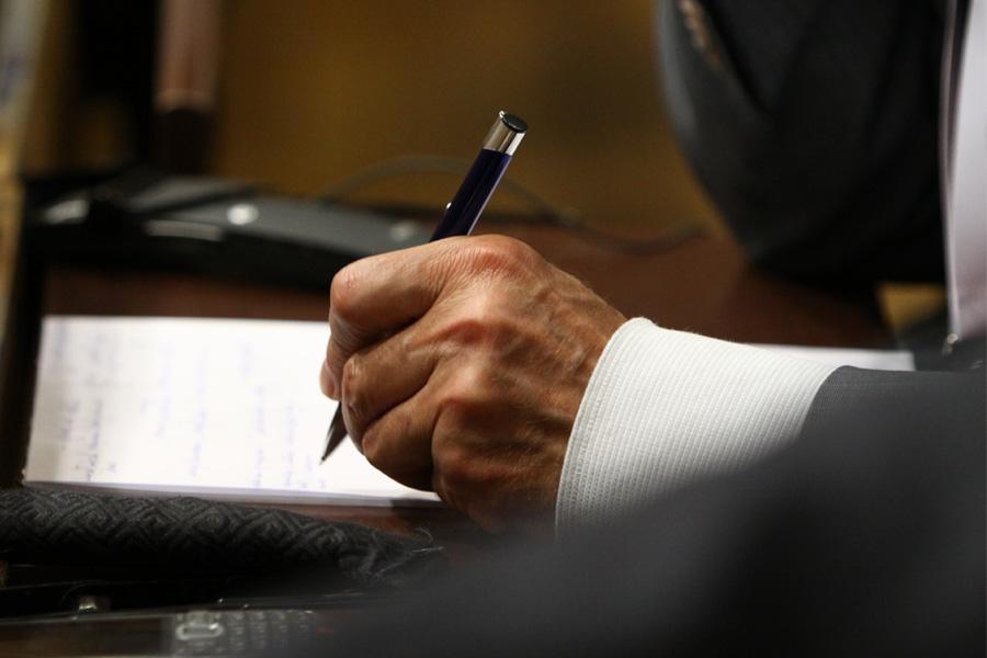 Długopis w dłoni, notatnik