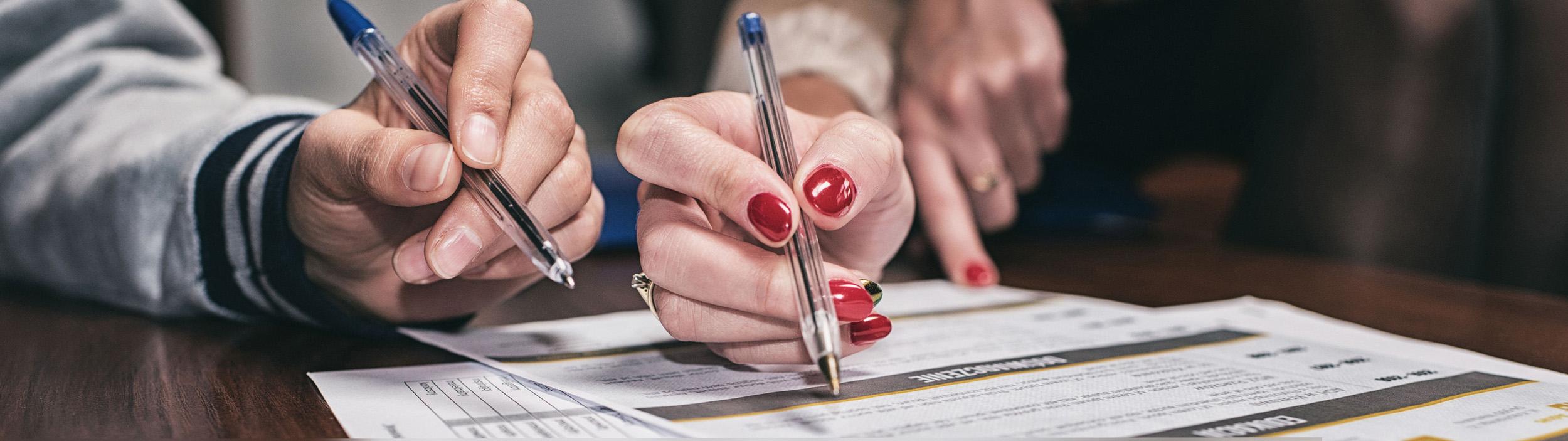 wypełnianie dokumentów, długopisy w dłoniach