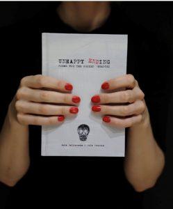 """zbliżenie na dłonie kobiety trzymającej książkę pt. """"Unhappy ending"""""""