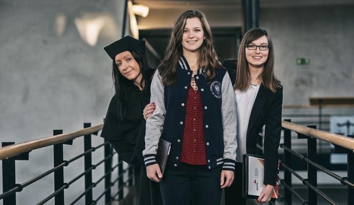 trzy dziewczyny, które stoją w holu Wydziału Humanistycznego w Sosnowcu. Stojąca w środku ma na sobie bluzę UŚ. Znajdująca się po jej lewej stronie ubrana jest w togę, a znajdująca się po prawej stronie dziewczyna ma okulary i trzyma teczkę