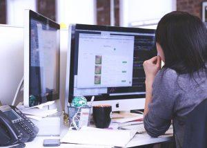 kolorowe zdjęcie: dziewczyna siedząca przy biurku, na którym stoją dwa monitory. Przed nią leżą porozkładane luźno kartki papieru.