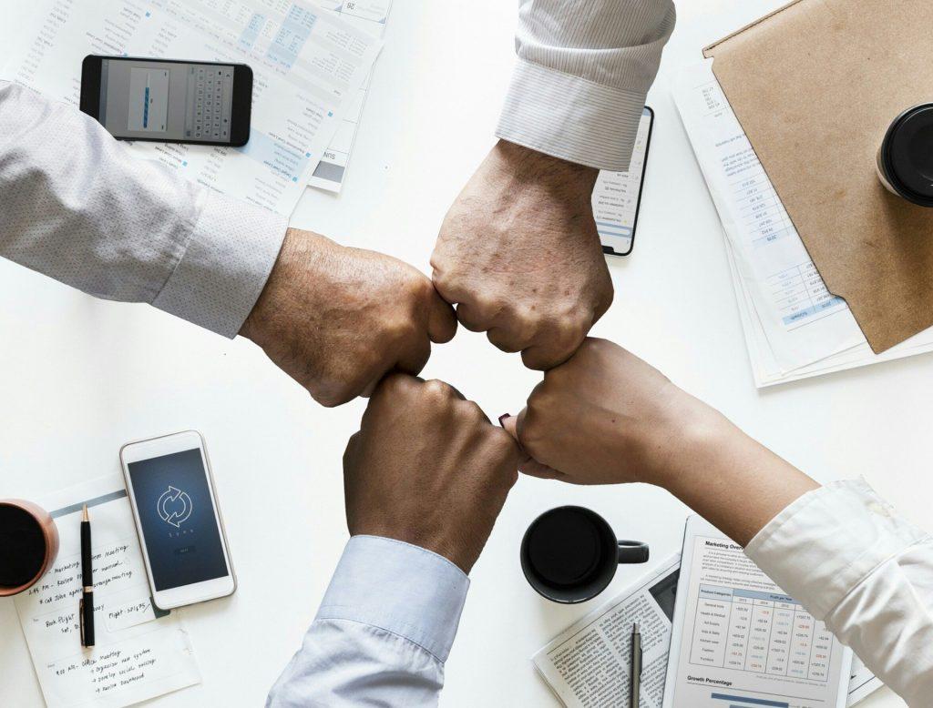 ręce czwórki ludzi stykające się pięściami nad stołem, na którym leżą dokumenty, telefony i kubki z kawą