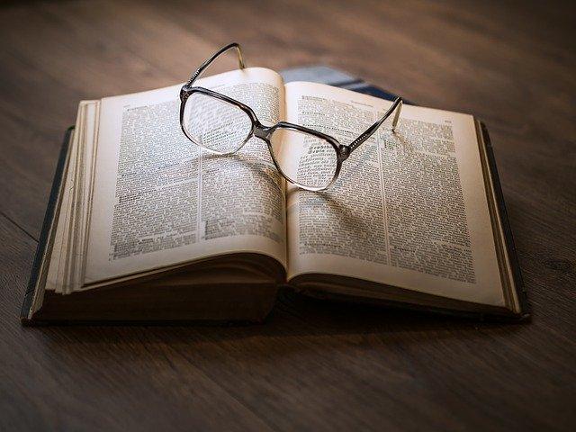 kolorowe zdjęcie przedstawiające okulary leżące na otwartej książce