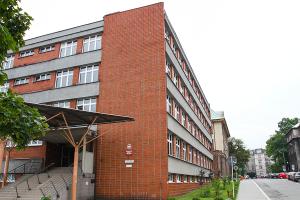 czteropiętrowy budynek, w kształcie prostokąta, elewacja w kolorach szaro-ceglanych